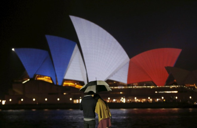 A couple stands in the rain as the blue, white and red colours of France's national flag are projected onto the sails of Sydney's Opera House in Australia November 14, 2015 following the attacks in Paris.    REUTERS/Jason Reed