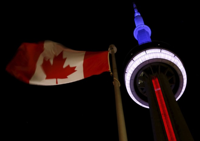 The landmark CN Tower is lit blue, white and red in the colors of the French flag following Paris attacks, in Toronto November 13, 2015. Canadian Prime Minister Justin Trudeau said on Friday it was too soon to say whether the deadly attacks in Paris would prompt him to reconsider his pledge to withdraw Canada from airstrikes against Islamic State militants in the Middle East. REUTERS/Chris Helgren